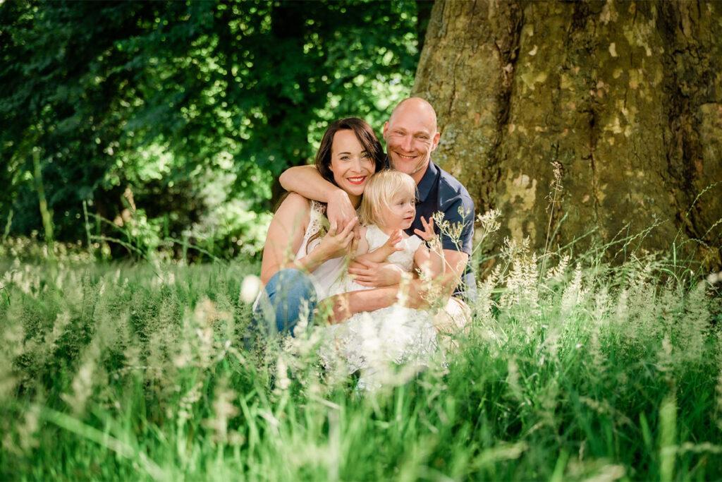 Familienfoto im Grünen mit Kind im Sommer