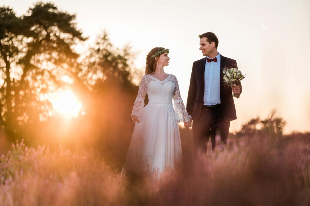 Hochzeitspaar auf dem Abendspaziergang in der Heide