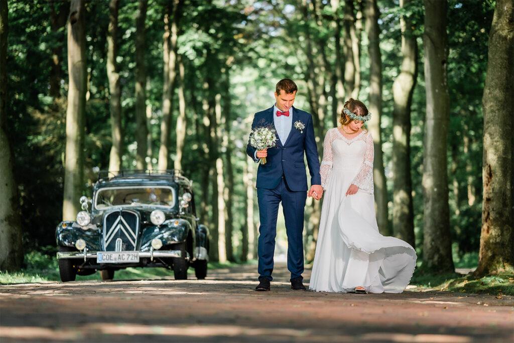 Brautpaar steigt aus dem Oltimer und geht spazieren