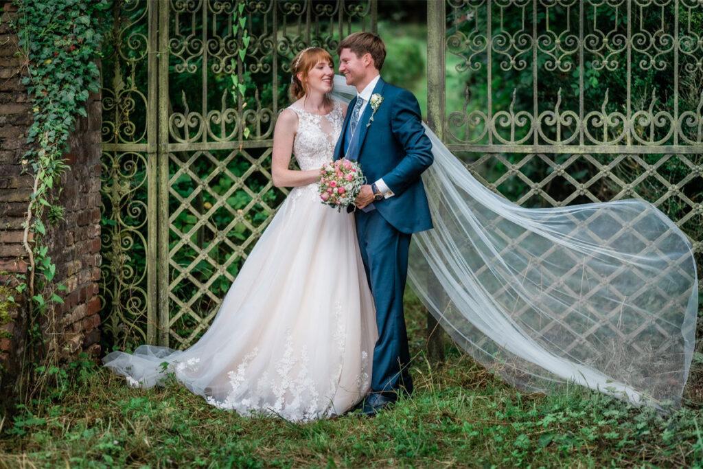 Hochzeitspaar mit Brautstrauss steht an einem Tor
